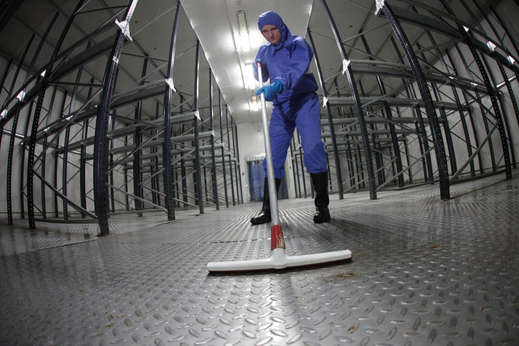 29864976 - worker in blue, protective  uniform cleaning floor in empty storehouse - fish eye lens