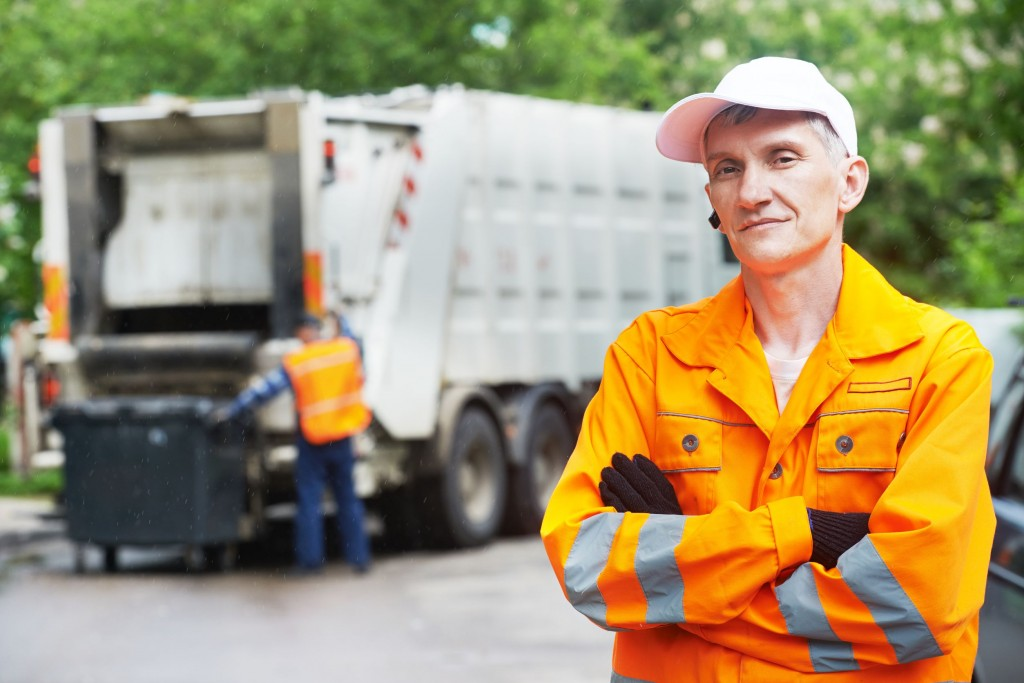 22801903 - portrait of municipal worker recycling garbage collector truck loading waste and trash bin