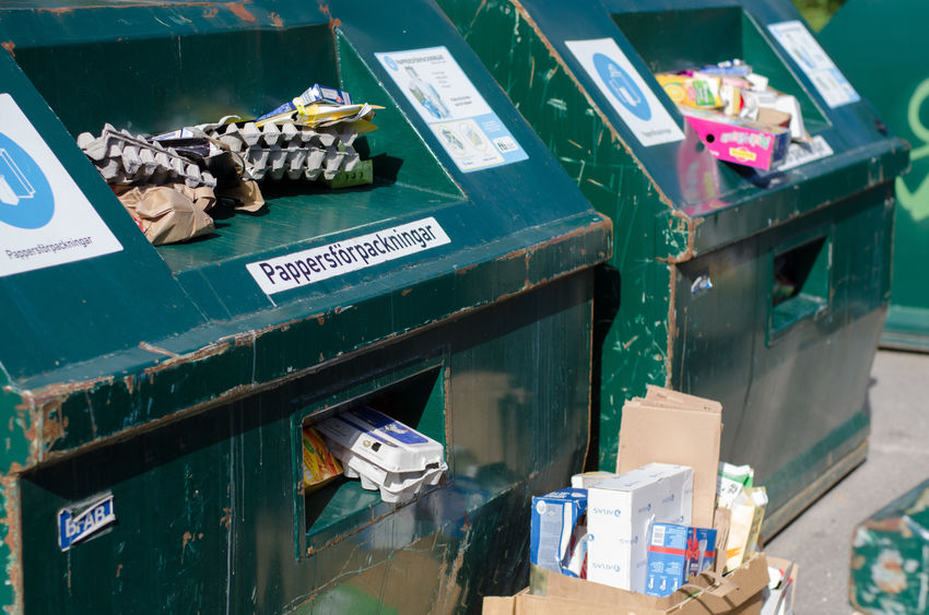 Green recycling containars full with paper and boxes at an environmental station in Soderhamn, Sweden - July 18 2017